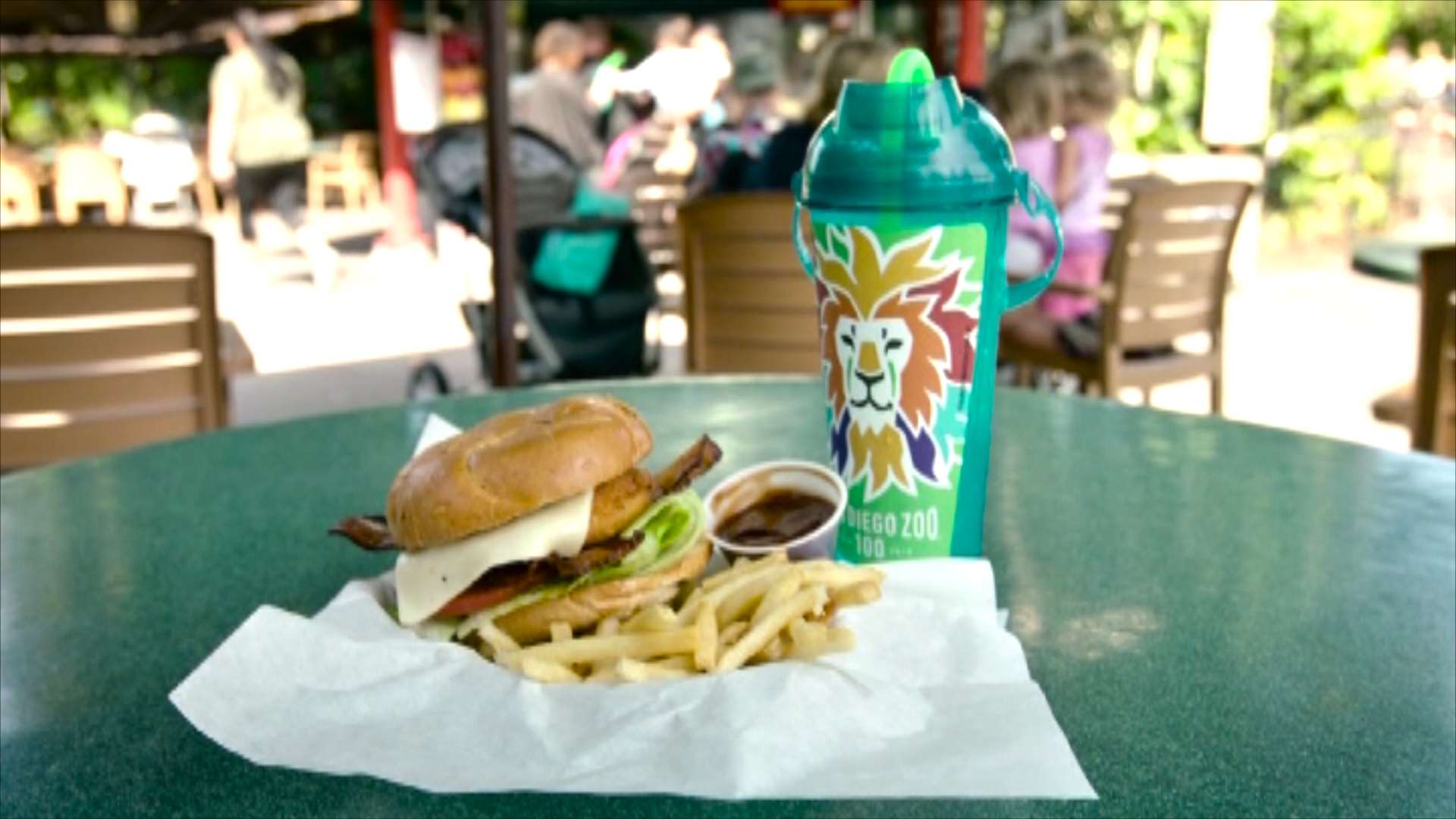 Image of a burger, fries, and a large custom souvenir cup with lid and straw